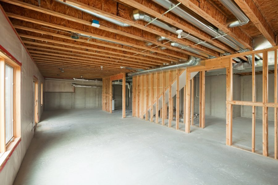 """An unfinished walk-out basement in a large two-story or ranch house. Basements are often left looking like this after initial construction, a cost saving move which allows for future expansion. This image would make a good starting point for a remodeling or house completion concept. The floor and right exterior wall are poured concrete, the left wall is framed, insulated and covered with plastic. The floor joists are engineered I-beams. Some broken concrete is visible behind the far wood frame wall."""